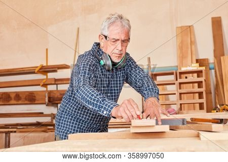 Experienced carpenter or carpenter at the workbench during the woodworking
