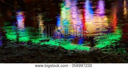 Colorful colors from the fair or fun fair reflect in a puddle in the evening when it rains