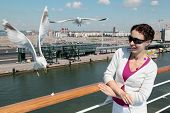 Smiling woman in white suit and dark sunglasses feeds seagulls on deck of ship poster
