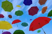 flying of multicoloured umbrellas on a background blue sky with clouds poster