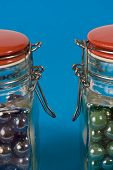 Two glass jars with red lids on blue background poster