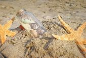 starfish and bottle in sand on the beach poster