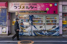 Tokyo, Japan - Mar 18, 2019: Elderly Japanese Man Wearing Face Mask Walking Past Row Of Vending Mach
