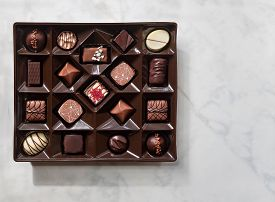 Top View Of Box Of Chocolates On Light Background.