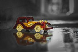Reflection Vintage Toy Car Under The Rain On The Road. Miniature Car Toy Reflection In Rain. Reflect