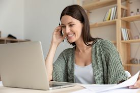 Smiling Female Employee Laugh Watching Webinar On Laptop