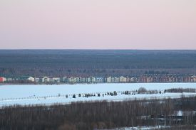 Winter Landscape With A Line Of Cottage Houses Against The Backdrop Of The Sunset Sky And Forest Mas