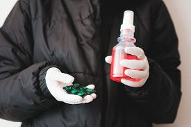 Girl In Protective Gloves Holds An Antiseptic With Pills. Close-up