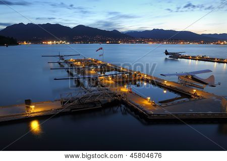 Dawn at the Vancouver floatplane base in Coal Harbor, Burrard Inlet at the new convention center with the Coast Mountains in the background. BC. Canada. poster