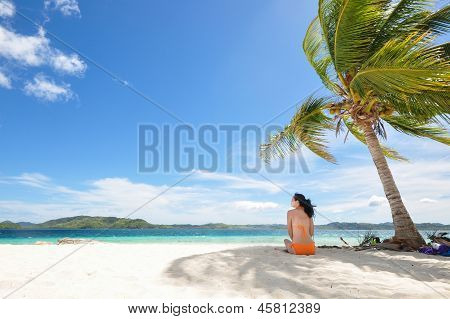 Single young bikini girl sits in the shadow of a coconut tree on white beach , with clean background of beautiful blue sky and cloudscape and. Shot on Pass Island, Coron, Palawan, Philippines poster