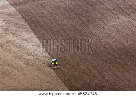 Um trator ajuntar um campo lavrado em preparação para a semeadura da lavoura de anos.