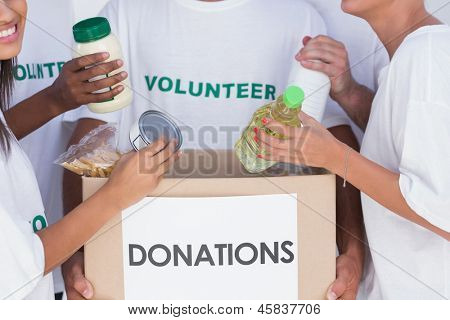 Group of volunteers putting food in donation box
