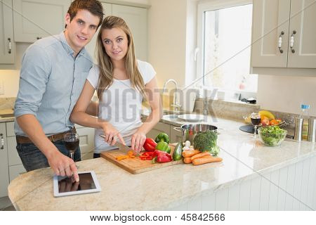 Man pointing on tablet pc wtih woman choppping peppers in kitchen