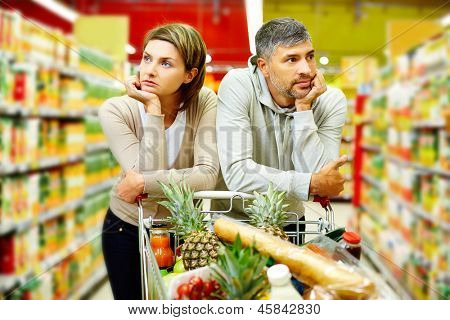 Image of young couple with cart in supermarket