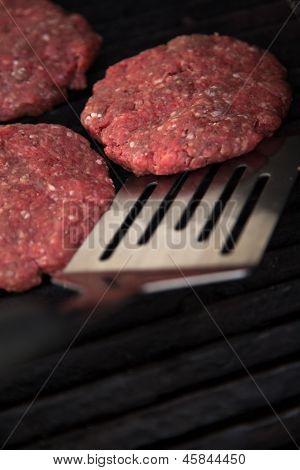 Raw Hamburgers On The Grill