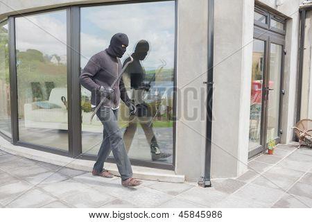 Burglar with cro bar outside home