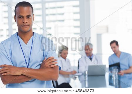 Serious doctor with arms crossed standing in front of his team