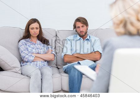 Upset couple sit on a sofa with arms crossed during a psychotherapy