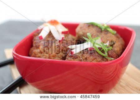 Three Meatballs In A Red Bowl With Condiments.