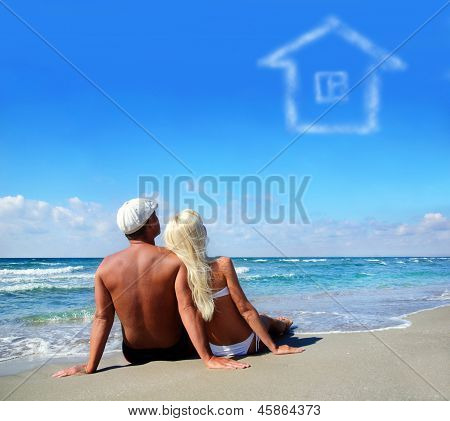 Young Couple On Sea Sand Beach Dreaming About The Own Home