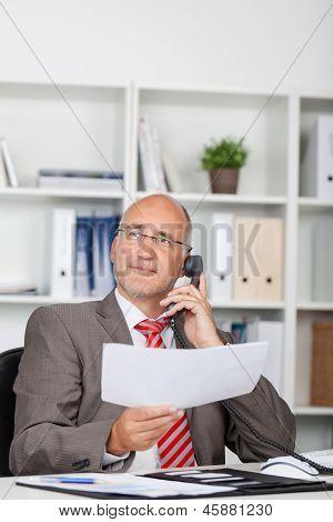 Businessman Holding Document While Using Landline Phone