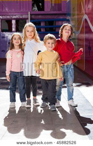Full length portrait of cute little boy standing with friends in kindergarten