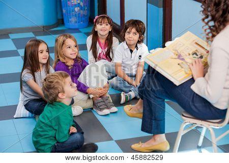 Teacher reading story book to children in kindergarten poster