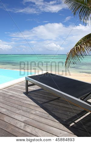 Infinity pool with deck chair by the beach