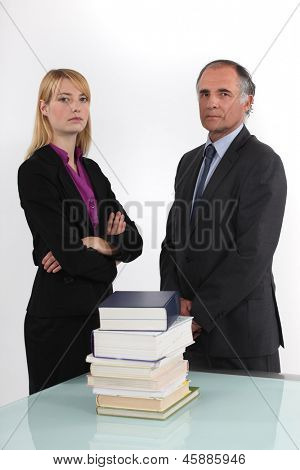 serious businessman and businesswoman posing next to pile of books
