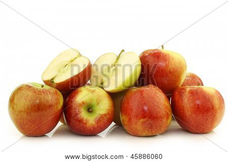 bunch of braeburn apples and a cut one on a white background
