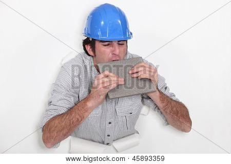 Fed-up tradesman biting a tile