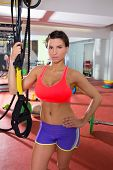 Crossfit fitness woman standing at gym holding trx posing poster