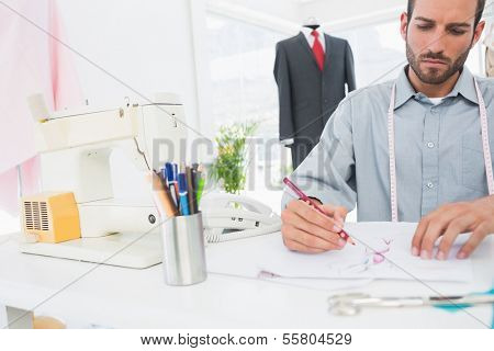 Young male fashion designer working on his designs in the studio