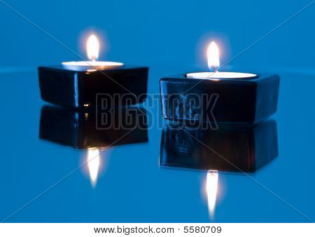 Two Burning Candles On Mirror Surface Of The Blue Colour
