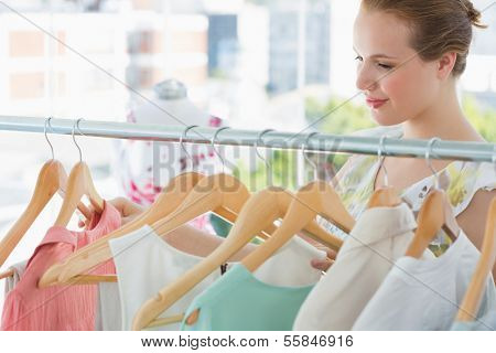 Close-up of a smiling female customer selecting clothes at clothing rack in store