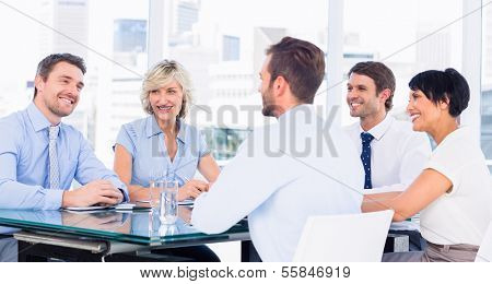Smartly dressed young executives sitting around conference table in office