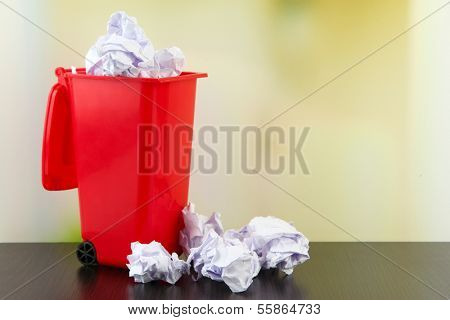 Crumpled paper balls in trashcan on table on bright background