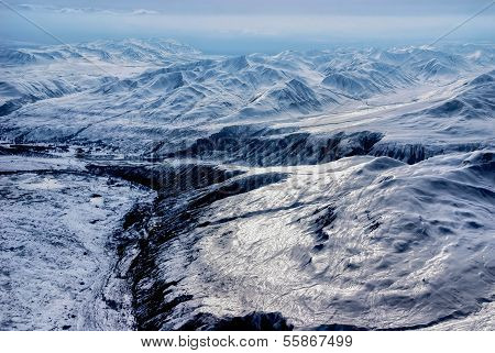 Snow-pack on Craggy Mountain Peaks and River Valley with Clouds.  Aerial View of Denali National Park, Alaska.  A Beautiful Wilderness Snowscape of Rock, Snow, and Ice. poster