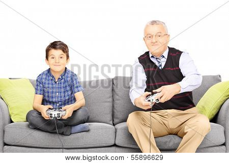 Grandfather with his nephew seated on a modern sofa playing video games isolated on white background