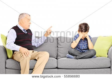Angry grandad shouting at his nephew, seated on a sofa, isolated on white background