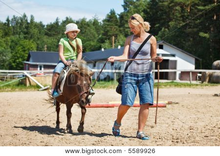 Little girl smiling and riding pony woman leading pony by bridle poster