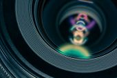 Macro shot of front element of a camera lens with beautiful color lights reflections poster