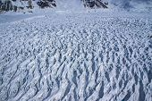 Aerial View of a Frozen River of Ice in the Great Alaskan Wilderness, Denali National Park, Alaska.  A Beautiful Snowscape of Rock, Snow, Water and Ice.  One of many glaciers flowing from mountains. poster