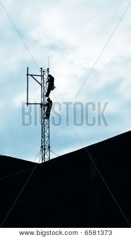 This photograph represent an installation of a GSM antenna performedby two workers poster