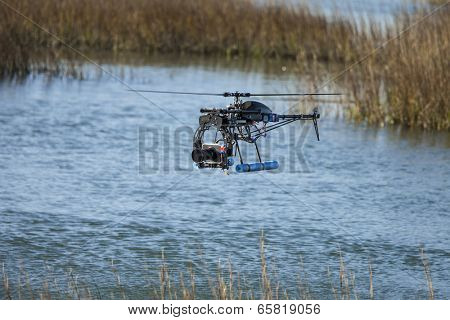 remote controlled drone with camera over water poster