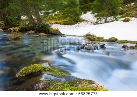 rural river with motion of flowing water over moss and rocks in forest