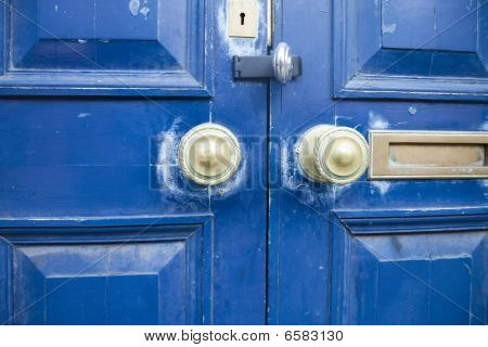 A blue door with bronze doorknobs mailslot and keyhole. The scuffed and faded paint together with the slightly askew door panels has a grungy feel to it. poster