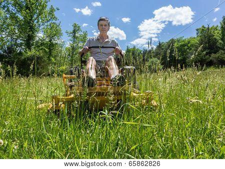 Senior Man On Zero Turn Lawnmower In Meadow