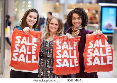 Excited Female Shoppers With Sale Bags In Mall