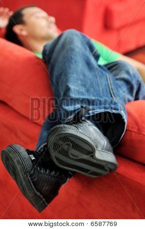 Hombre relaja en el sofá